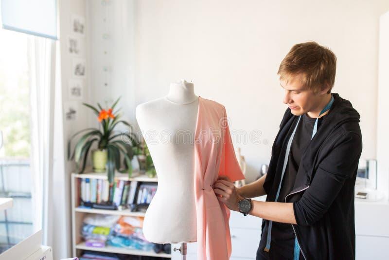 Stilista con il vestito di fabbricazione fittizio allo studio immagini stock