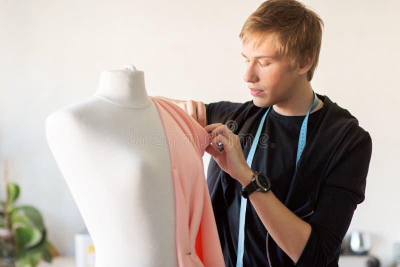 Stilista con il vestito di fabbricazione fittizio allo studio fotografie stock