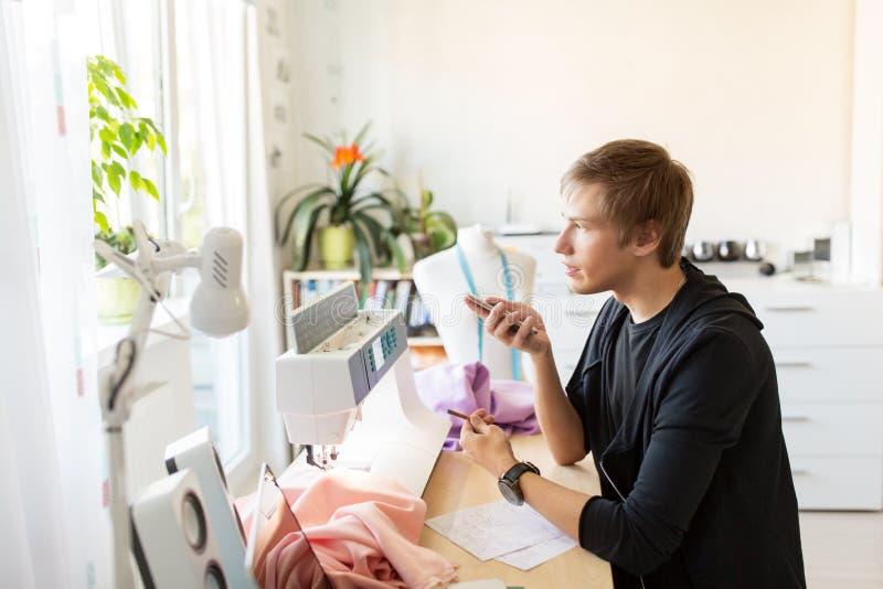Stilista con lo smartphone che funziona allo studio fotografia stock libera da diritti