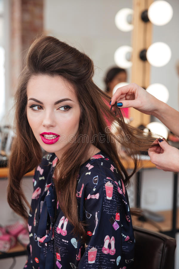 Stilista di capelli che fa pettinatura per modellare seduta nel salone di bellezza fotografie stock