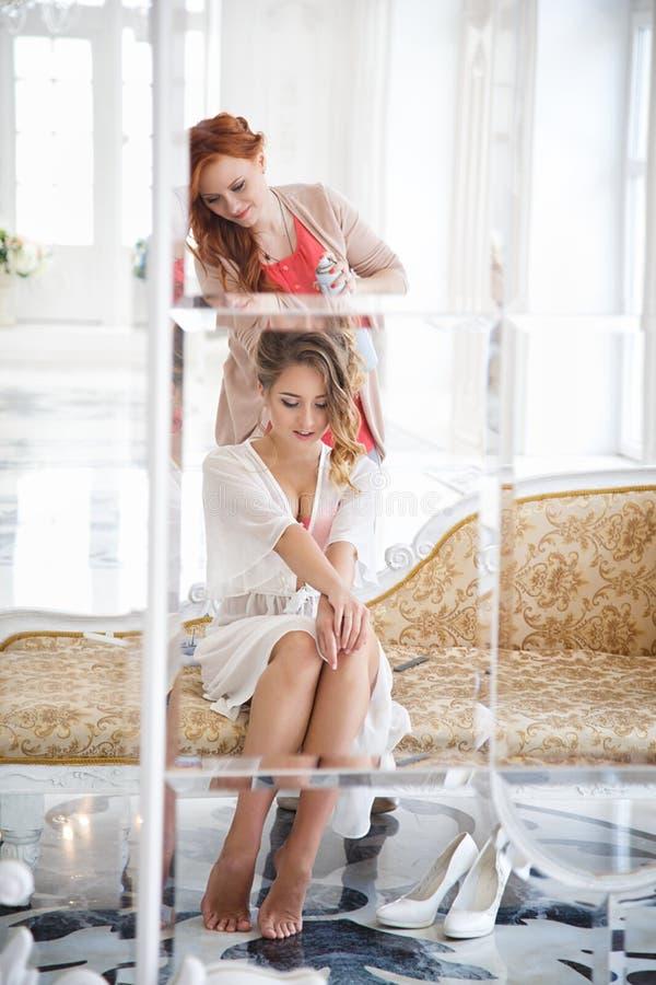 Stilista di capelli che prepara bella sposa prima delle nozze fotografie stock