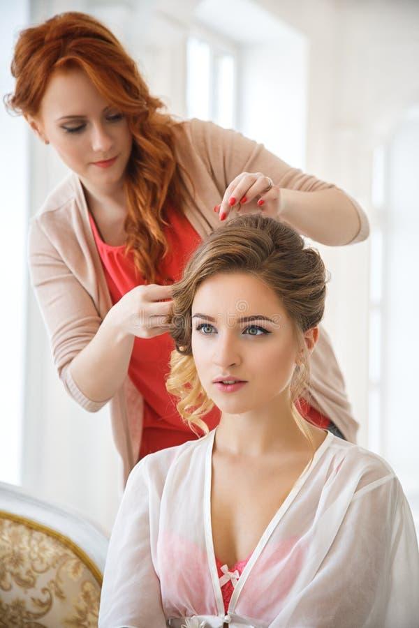 Stilista di capelli che prepara bella sposa prima delle nozze immagine stock libera da diritti