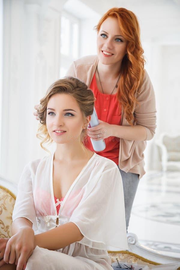 Stilista di capelli che prepara bella sposa prima delle nozze fotografia stock