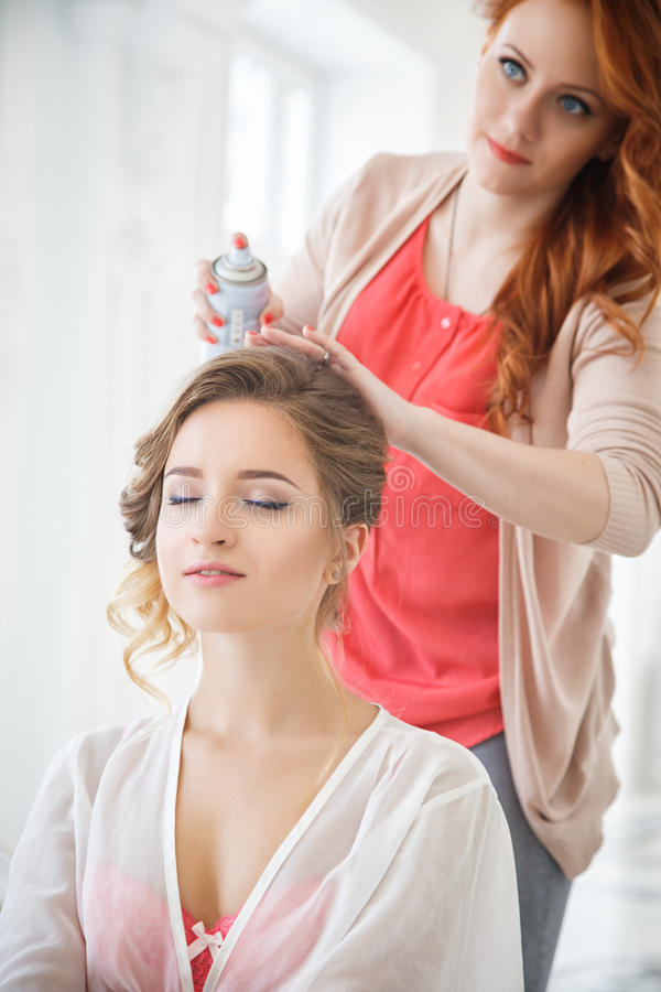 Stilista di capelli che prepara bella sposa prima delle nozze immagini stock