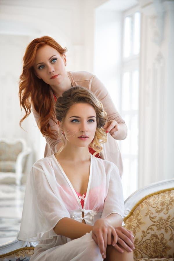 Stilista di capelli che prepara bella sposa prima delle nozze fotografie stock libere da diritti
