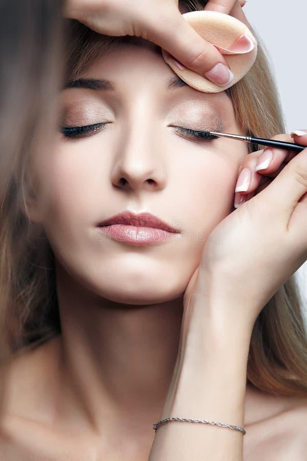 Stilista femminile - visagist che fa trucco dell'occhio alla giovane femmina fotografia stock