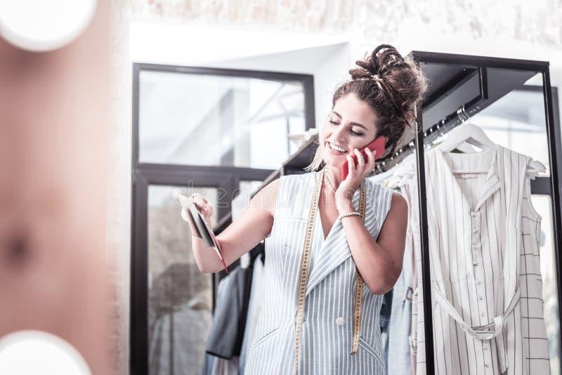 Stilista laborioso che chiama i suoi partner mentre scegliendo i nuovi tessuti fotografia stock libera da diritti