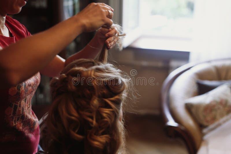 Stilista professionista che fa acconciatura per la bella donna, bionda immagini stock libere da diritti