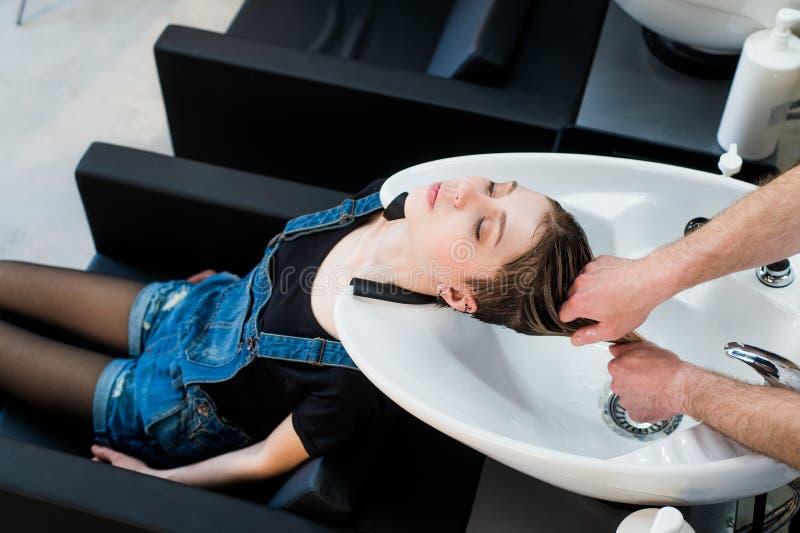 Stilista sul lavoro - capelli di lavaggio del parrucchiere al cliente teenager della ragazza prima di fare acconciatura fotografie stock libere da diritti
