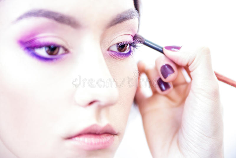 Stilisthand die oogsamenstelling toepassen op de oogleden van een jong mooi model stock afbeelding