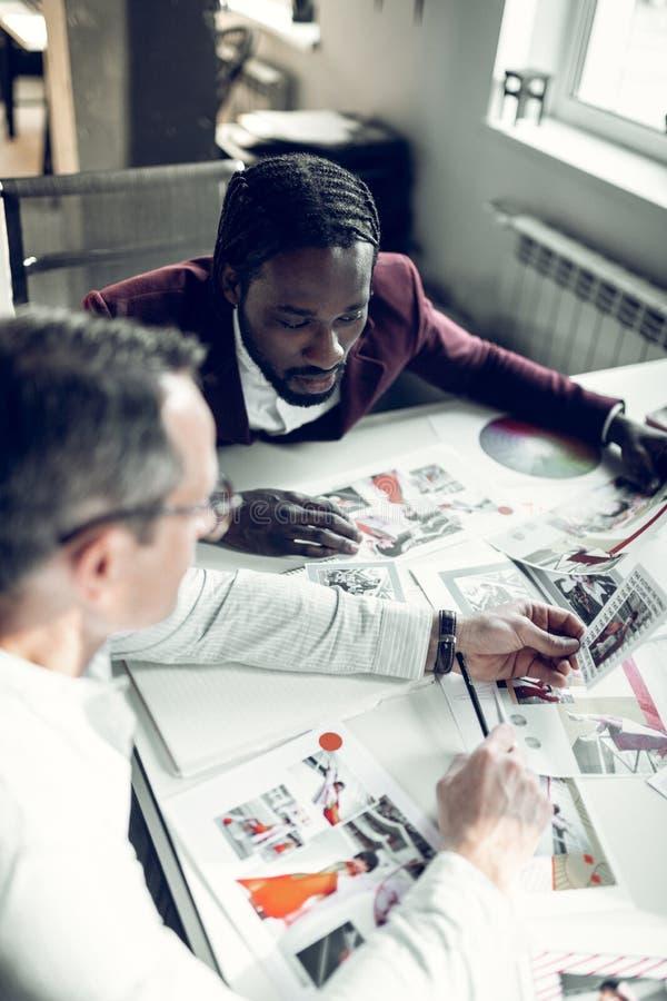 Stilisti maschii che esaminano le foto dei modelli immagini stock