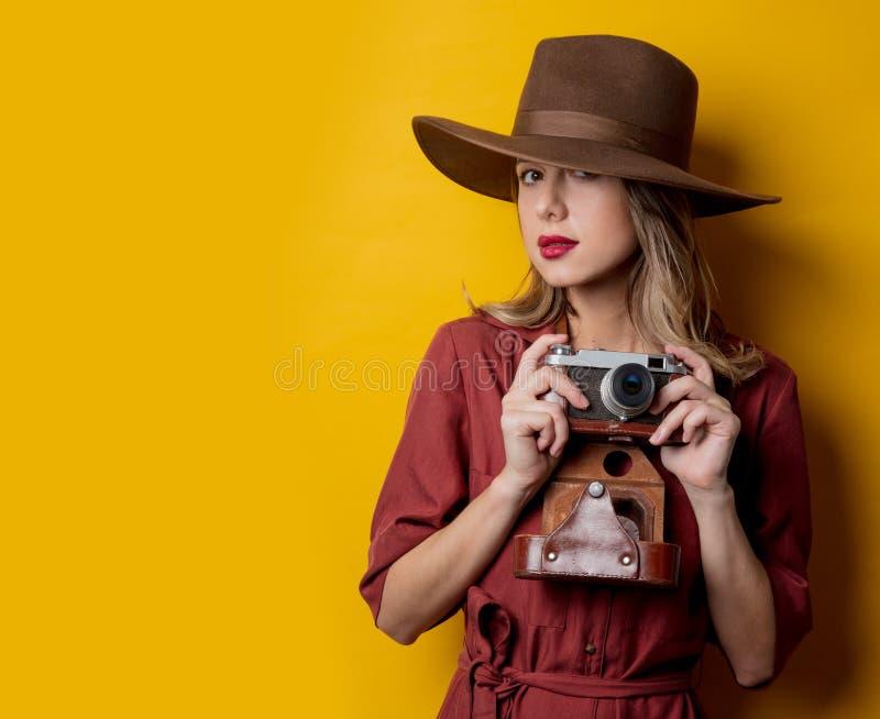 Stilkvinna i hatt med tappningkameran arkivbilder