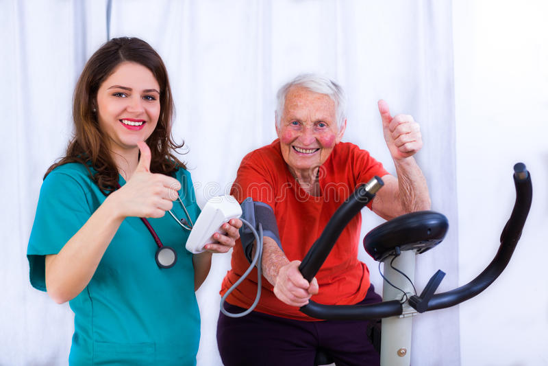 Still got it. Elderly women doing sport effort on a spinning bike having hear hart rate and blood pressure monitored royalty free stock image