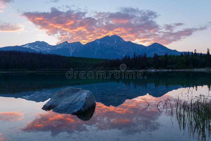 Still lake and mountain at sunset, with red clouds royalty free stock photography