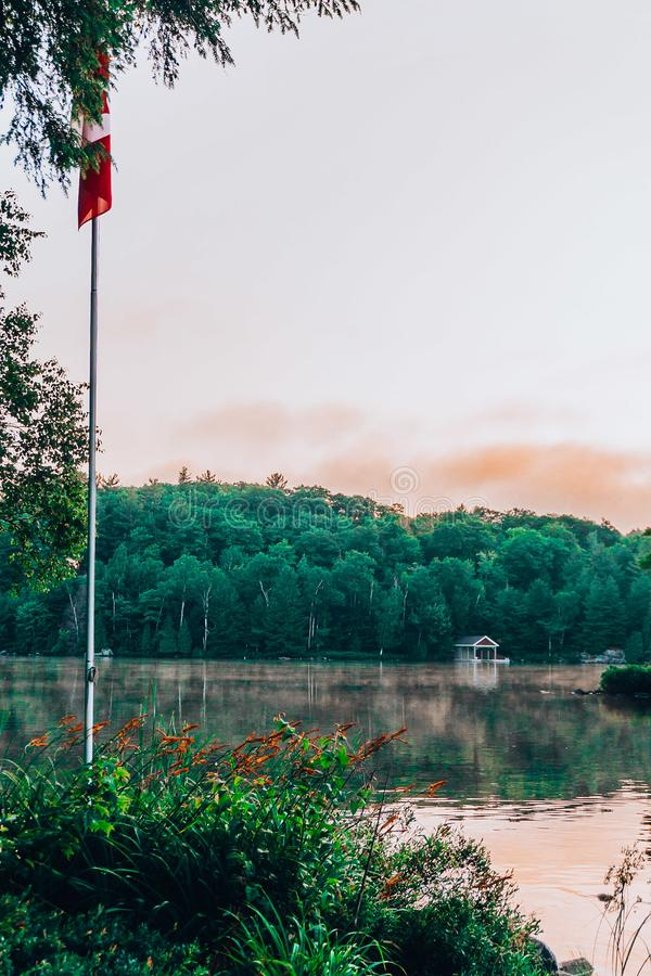 A still lake at sunset. With pink and blue skies and the canadian flag beside it and a foggy lake royalty free stock photo