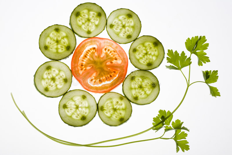 Still life. Image of cucumber slices around tomato piece with sprig of parsley near by royalty free stock photos