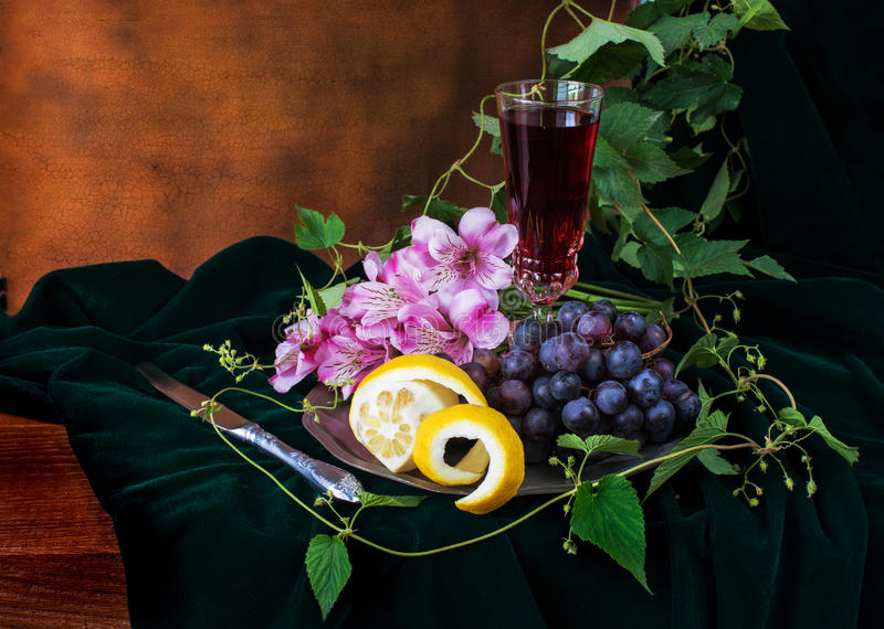 Still life in antique style. With a glass of wine, grapes and two lemons royalty free stock photography