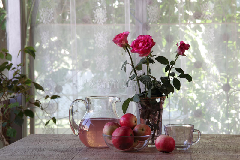 Still-life with apples, a bouquet of roses and apple compote stock photography