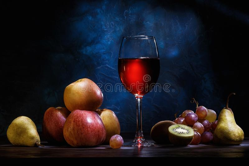 Still life, apples, grapes, fruit and red juice on a dark blue background. Diet, healthy eating royalty free stock photos
