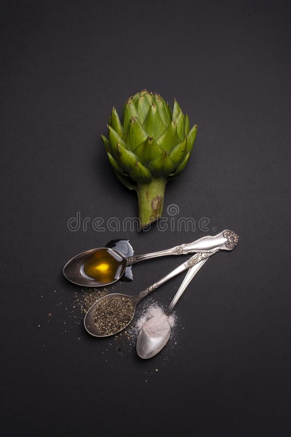 Still life with artichoke, salt, pepper, and oil stock images