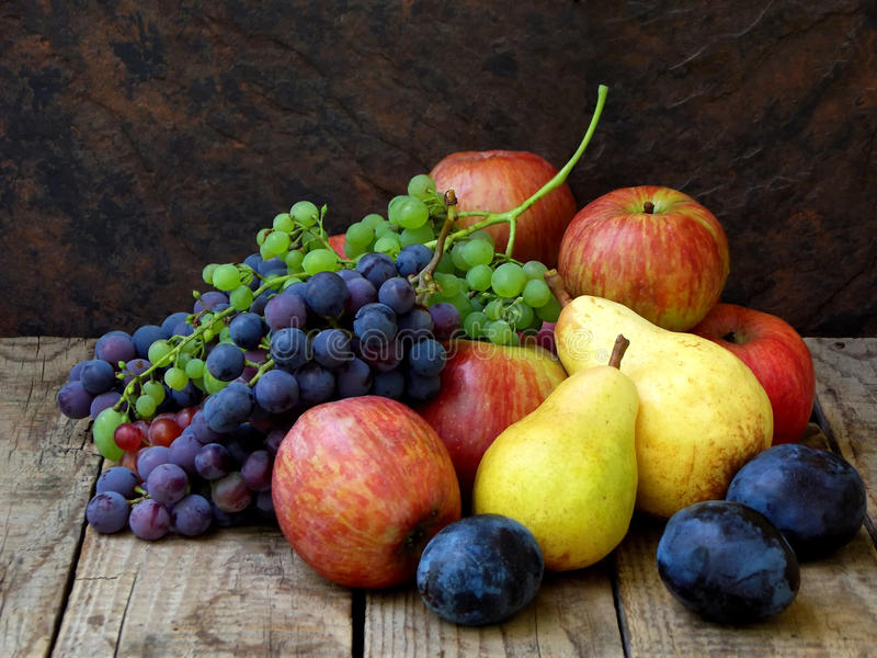 Still life of autumn fruits: grapes, apples, pear, plum stock image