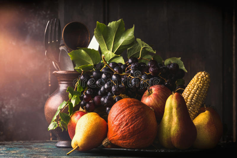 Still life with autumn fruits and vegetables: apples, pears, grapes, pumpkins, corn on the cob on dark rustic kitchen table stock photography