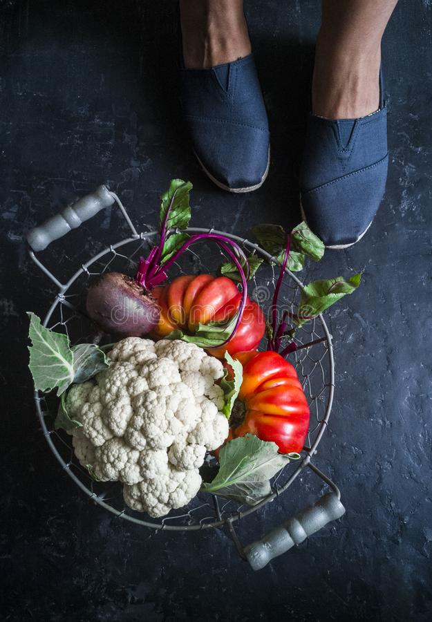 Still life with a basket of vegetables and women`s feet in sneakers on a dark background, top view. Cauliflower, tomatoes, beets royalty free stock photo