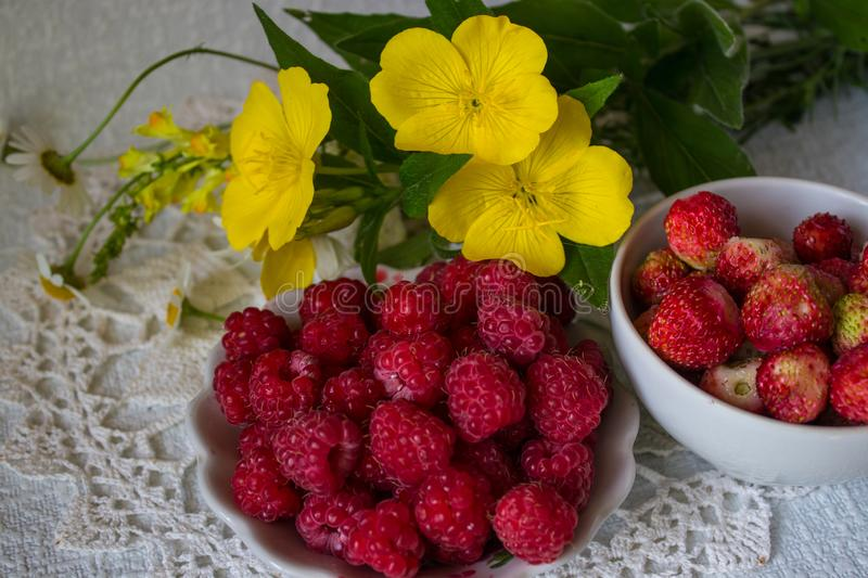 Still life with berries and flowers on a white napkin royalty free stock photos