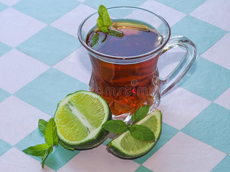 Still life of black tea in a glass cup, mint leaves and lime on the background of the table. stock photography