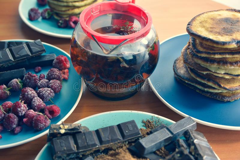 Still life on blue plates pancakes with peas, grated chocolate, chocolate bars, brewed tea royalty free stock photo