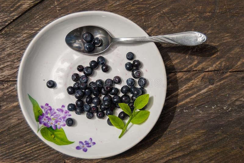 Still life of blueberries on a white plate table of rough boards stock photography
