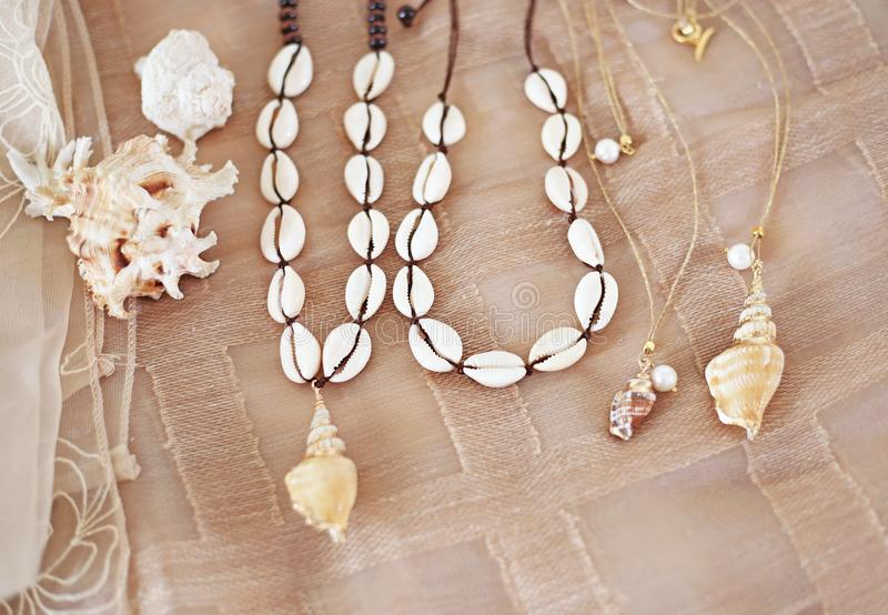 Bohemian summer jewelry with shells - cowrie shells necklaces - fashion jewelry advertisement. Still life of bohemian summer jewelry with shells - cowrie shells stock photo