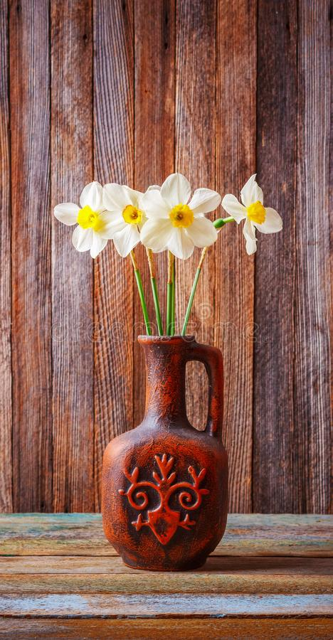 Still life of a bouquet of daffodils flowers in an old ceramic jug on a wooden vintage grunge background royalty free stock image