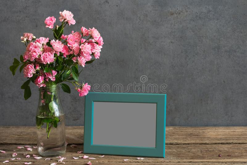 Still life with bouquet of pink rose flowers, blank photo frame and petals. mock up royalty free stock images