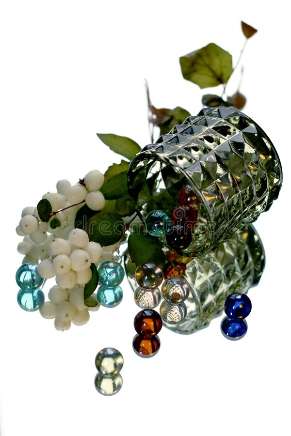 Still life with a branch of Symphoricarpos and glass balls. Still life with a branch of Symphoricarpos and colorful glass balls on a white background with stock image