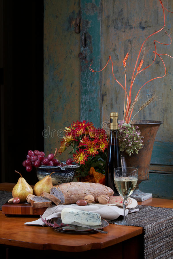 Still life of bread, wine, fruit, cheese. Still life on antique maple table with walnut bread, gorgonzola cheese, Bosc pears, nuts, red grapes and white wine stock photography