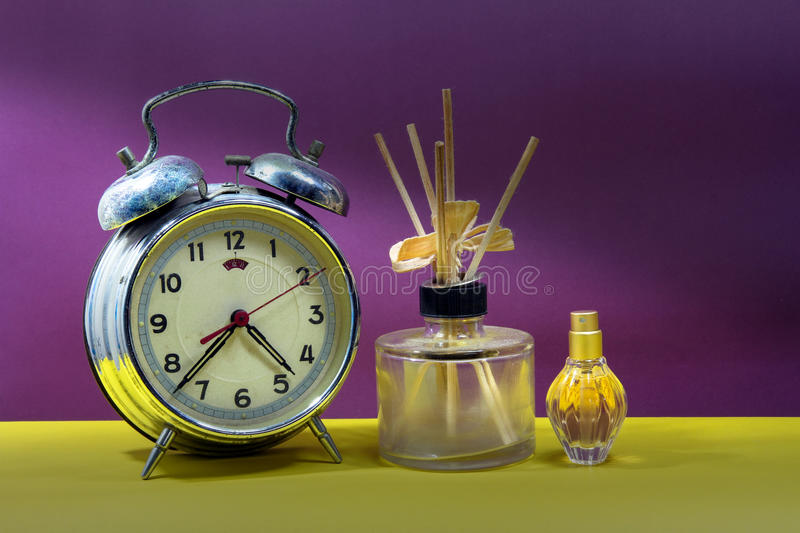 Still life with broken alarm clock, empty essential oil, classic. Perfume, colorful background royalty free stock images