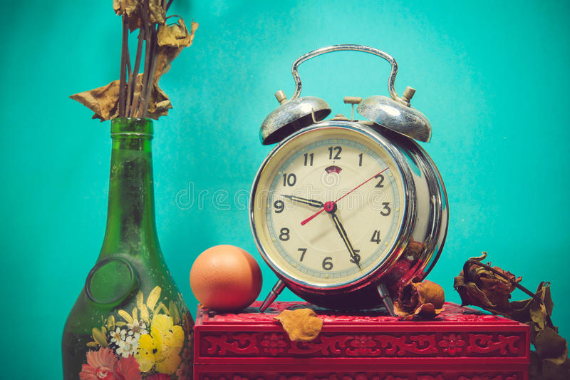 Still life with broken alarm clock, old glass vase with dead rose, egg, vintage box stock photos