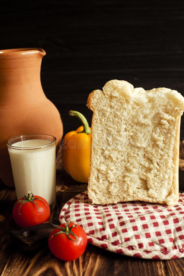 Still life on a brown and black background. In the photo, milk, hleb, jug, tomatoes and Balgarian pepper. royalty free stock photography