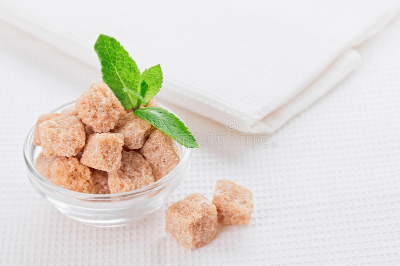 Still life with brown lump cane sugar, on white linen stock images