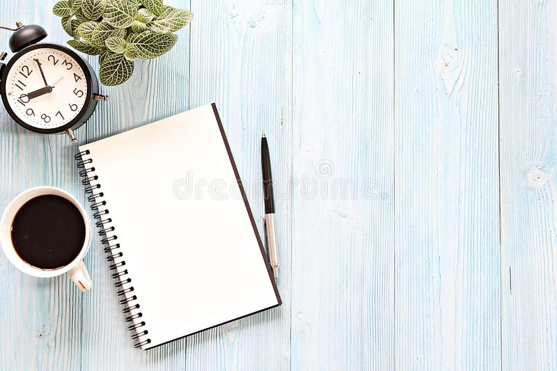 Open notebook with blank pages, coffee cup and clock on wooden desk table. Still life, business, planning or working concept : Open notebook with blank pages stock image