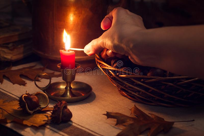 Still life with a candle, chestnuts and a hand royalty free stock photography
