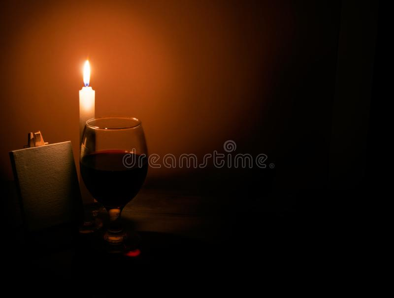 Still-life from a candle a glass of wine and an easel stock images