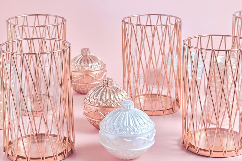 Still life of candles and candlesticks in rose gold on a pink background. close up stock photography