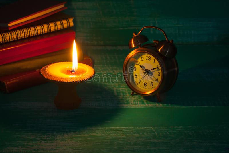 Still life candlestick on old book with alarm clock. On wood royalty free stock images