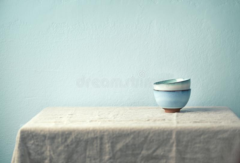 Still life with ceramic bowls on a tabel   laid with a linen cloth. Culinary concept stock photography