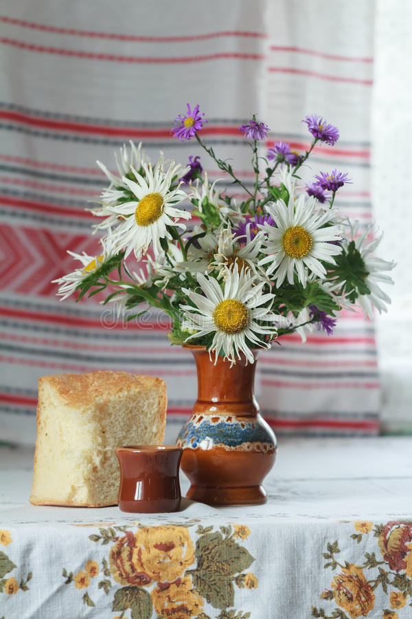Still life of ceramic vase and glass with cut lilac and white Aster flowers and slice of yeasted wheat bread. Still life of vase and glass with cut lilac and royalty free stock image