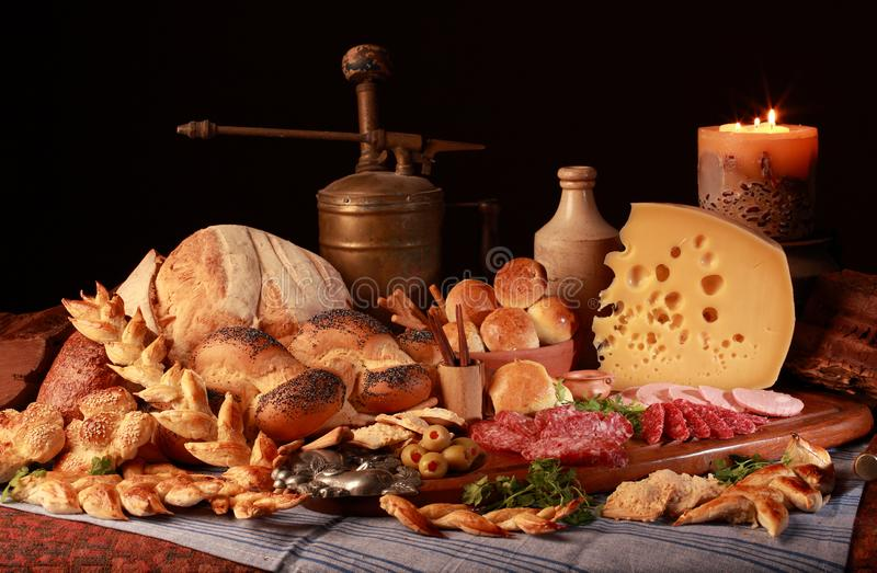 Still life with cheese, candle, italian salami, different types of bread, olives, etc. royalty free stock photo