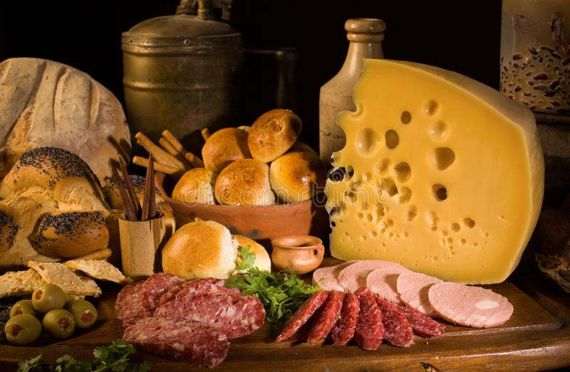 Still life with cheese, italian salami, different types of bread, olives, etc. royalty free stock photo