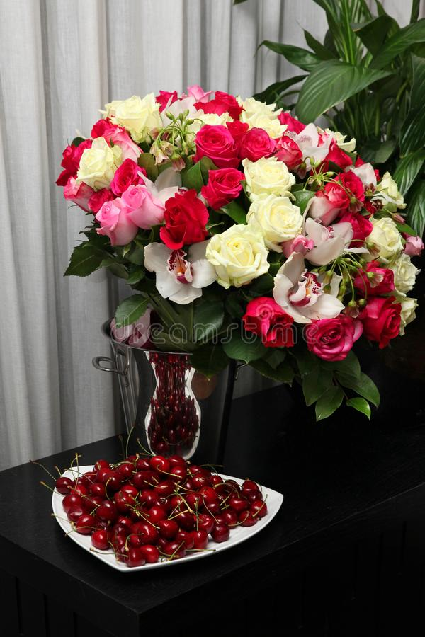 Still life of cherries and a gorgeous bouquet of roses royalty free stock photo